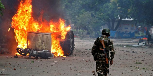 A member of the security forces walks towards a burning vehicles during violence in Panchkula, India,...