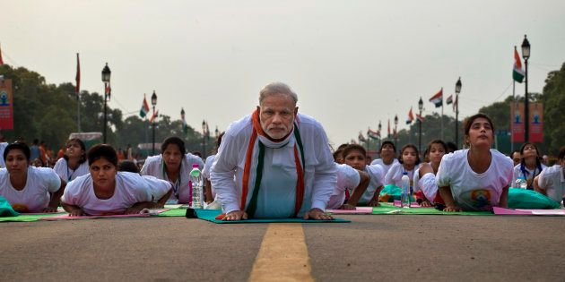 Indian Prime Minister Narednra Modi lies down on a mat as he performs yoga along with thousands of Indians...