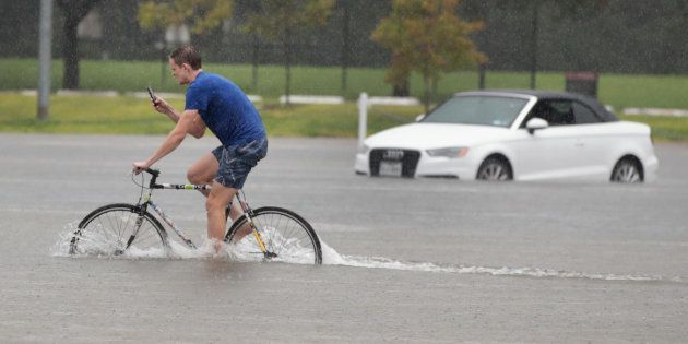 HOUSTON, TX - AUGUST 27: Cade Ritter rides through a flooded parking lot on the campus of Rice University...
