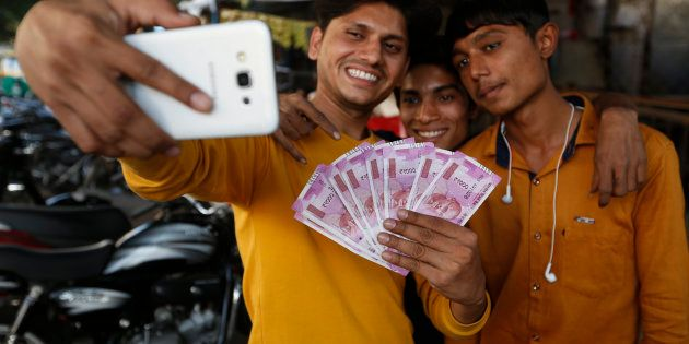 Indians takes selfie with new currency notes of 2000 Indian rupee in Ahmadabad, India, Friday, Nov. 11,...