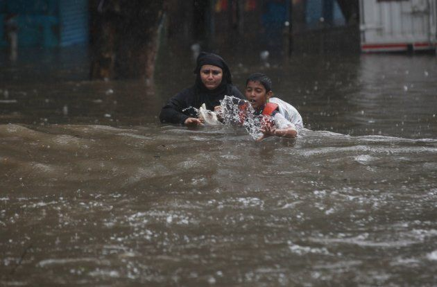 Indian people wade along a flooded street during heavy rain in Mumbai, India on August 29,