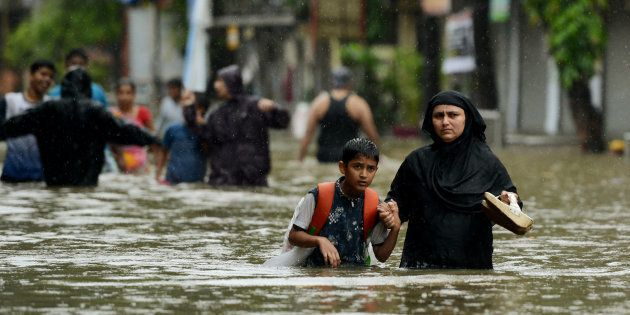 An Indian woman wades with her son through flooded street during heavy rain showers in