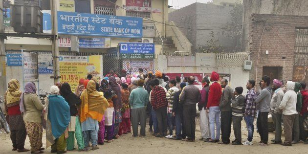 Despite cold weather people queuing outside the State Bank of India branch to get cash at Batala Road...