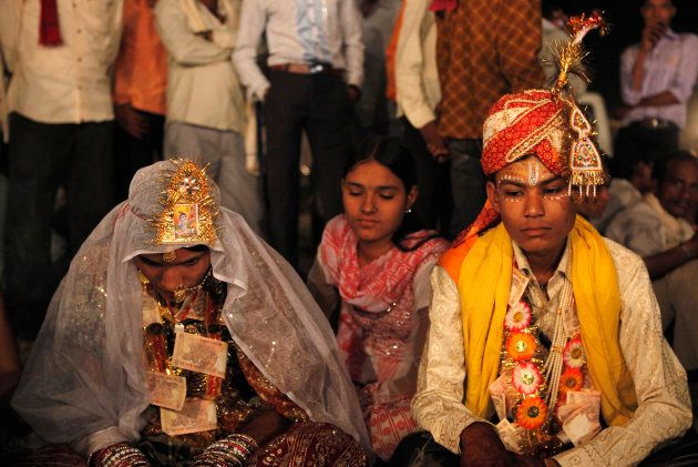 Hemant (R), 16, sits with his 13-year-old newly wed wife Saraswati in a mass marriage outside his village...