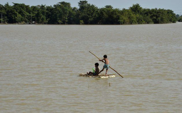 Indian children uses a raft to travel over flood waters in Araria in Bihar state on August 19,