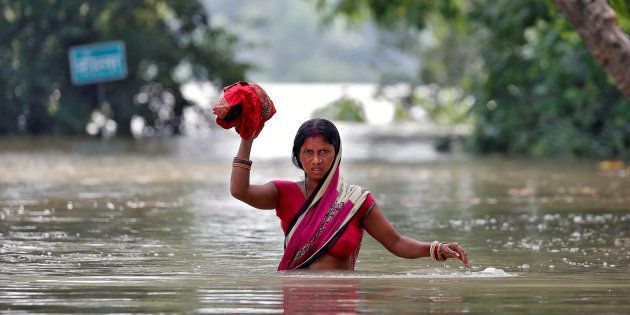 A woman wades through a flooded village in the eastern state of Bihar, India August 22, 2017. REUTERS/Cathal...