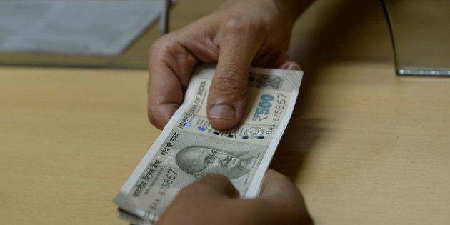 A bank staff member hands Indian 500 rupee notes to a customer on November 24, 2016, in the wake of the...
