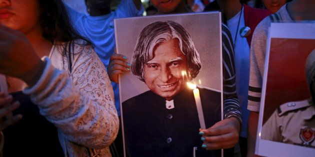 A student holds a portrait of former Indian President A. P. J. Abdul Kalam during a candle light march...