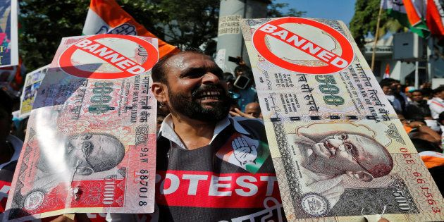 A man holds placards and shouts slogans during a rally organized by India's main opposition Congress...