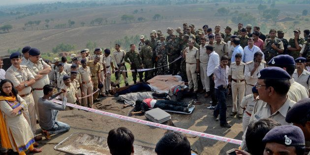 Police officers and Special Task Force soldiers stand beside dead bodies of the suspected members of...
