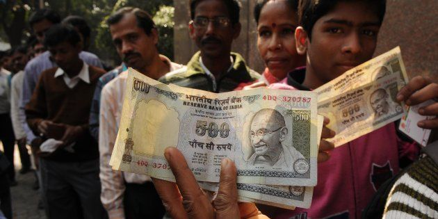 People in queue waiting outside bank with old 500 Rs. notes in front of