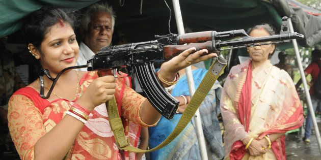 [REPRESENTATIONAL IMAGE] File photo of a housewife trying to hold an AK-47 rifle during an exhibition...