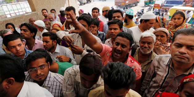 A man shouts at a bank manager urging him to open the bank's gate amidst a crowd waiting to deposit...
