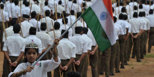 A child holding the national flag as Rashtriya Swayamsevak Sangh (RSS) volunteers line up ahead of a...