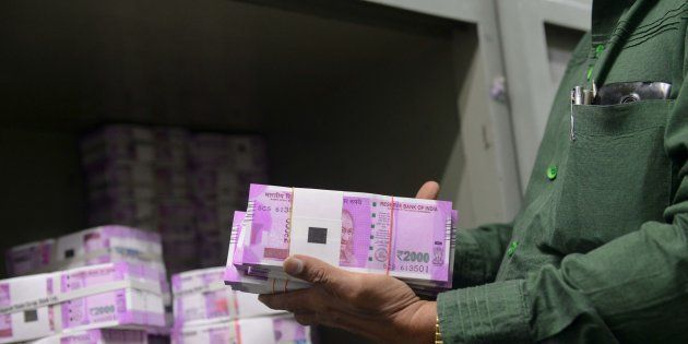 An Indian bank employee checks stacks of new 2000 rupee notes in