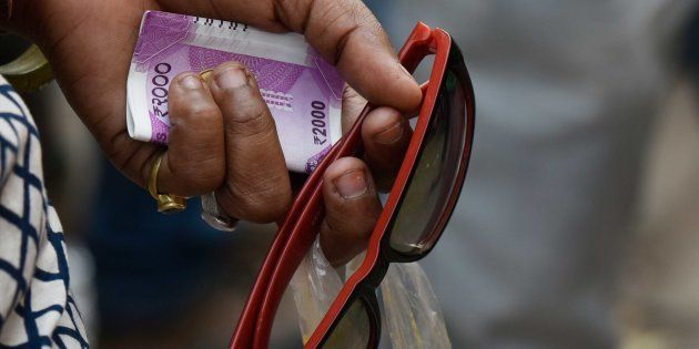 NEW DELHI, INDIA - NOVEMBER 13: A lady holds a 2000 rupee currency as she waits in a long queue to withdraw...
