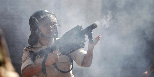 An Indian police officer fires tear gas towards protesters during a protest march in