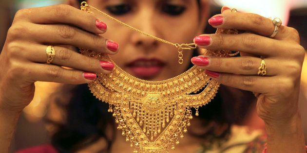 A salesgirl shows a gold necklace to customers at a jewellery showroom in the northern Indian city of...