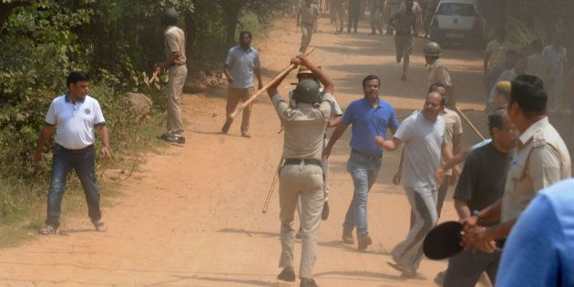 Police use lathis or batons to control protesters, who set fire to liquor shop near Ryan International...