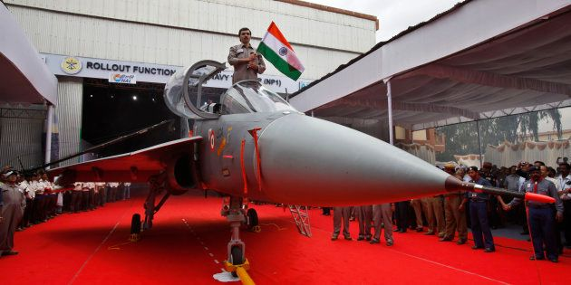 A Hindustan Aeronautics Limited engineer hurls the Indian flag as he stands in the cockpit of India's...