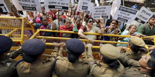 Activists from All India Democratic Women's Association (AIDWA) shout slogans behind a police barricade...