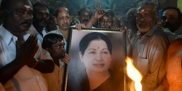 Supporters hold a photograph of Tamil Nadu state leader Jayalalithaa