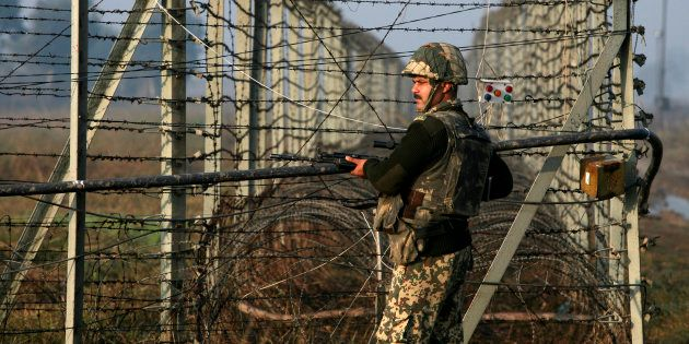 An Indian Border Security Force soldier patrols near the fenced border with Pakistan in Suchetgarh, southwest...