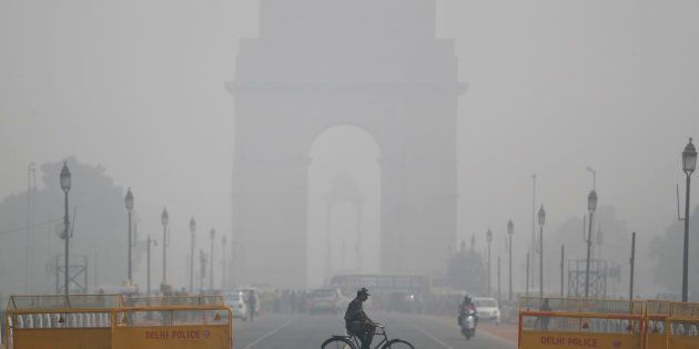 An Indian soldier rides a bicycle as past the India Gate monument on a fog enveloped morning in New Delhi,...