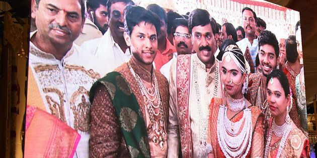 Indian mining tycoon, Gali Janardhan Reddy, (C) is seen on a big screen as he poses with his daughter...