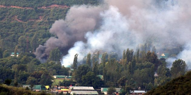 Smoke rises from the army base which was attacked by militants in the town of Uri, Kashmir on 18