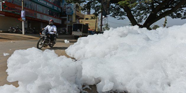 An Indian motorcyclist negotiates away from fluffy piles of foam at Varthur Kodi junction in east