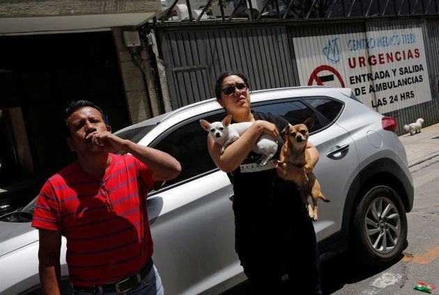 A woman carry her dogs while waiting outside their home after an earthquake in Mexico