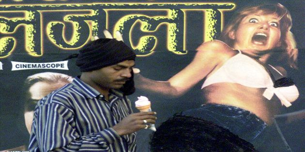 An Indian man passes a wall of a cinema displaying a poster of an adult movie in New