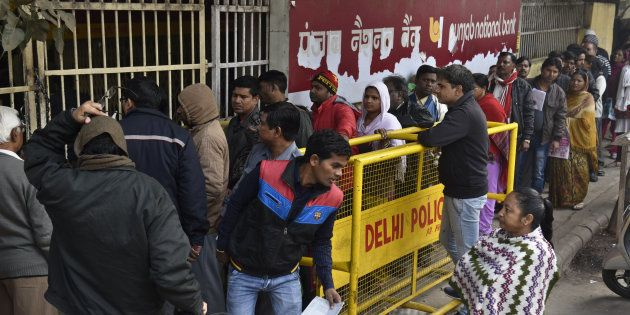 People queue up in front of Punjab National Bank to withdraw or deposit the money at Trilok