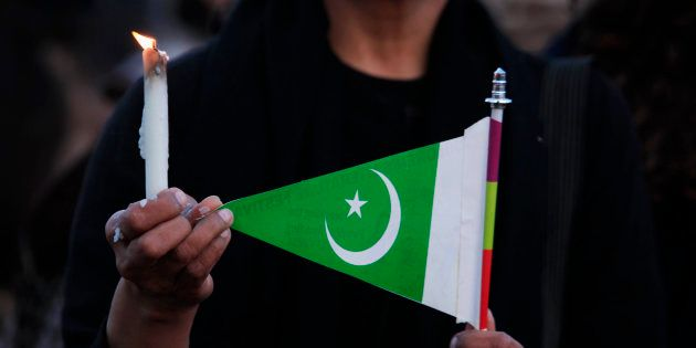 A woman holds a candle and a Pakistani flag as she takes part in a protest against terrorism in Islamabad...
