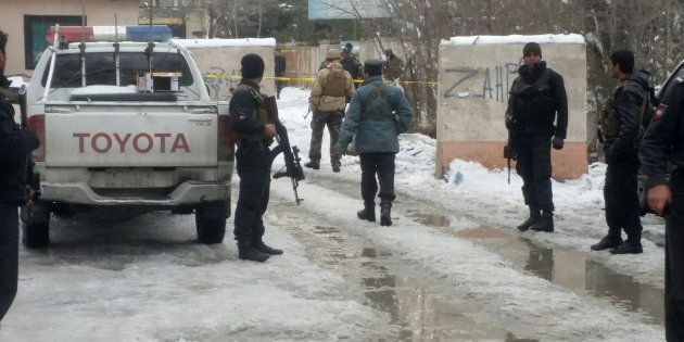 Afghan policemen keep watch at the site of a bomb blast in Kabul, Afghanistan February 7,