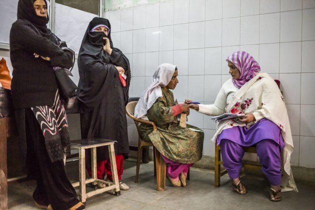 A Kashmiri patient speaks with a member of medical staff as she waits to be seen during a trauma and depression out-patient clinic, held by Dr Arshad Hussain.