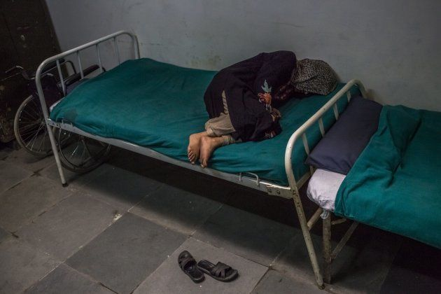 In this photo taken on November 20, 2015, Kashmiri patient Masrat Naz, 45, and who is suffering from symptoms of schizophrenia, lies on a bed as she periodically shouts to medical staff after being brought by relatives to the casualty ward at the Psychiatric Diseases hospital in Srinagar.
