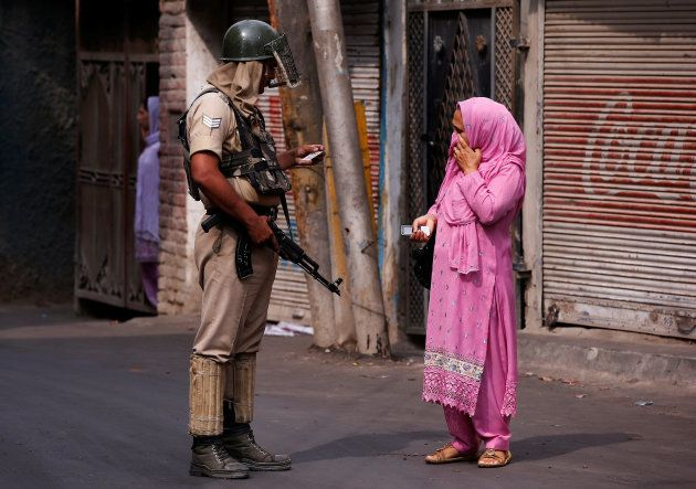 An Indian policeman checks an identity card of a woman during a curfew in