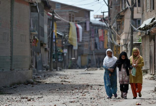 Two women and a girl make their way along a street littered with rocks thrown by protestors in Srinagar...