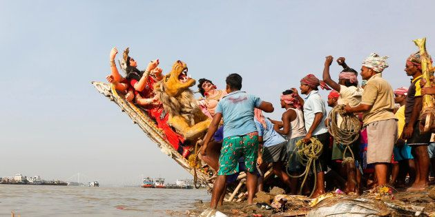 Devotees immerse an idol of the Hindu goddess Durga into the Ganges river after the end of the Durga...