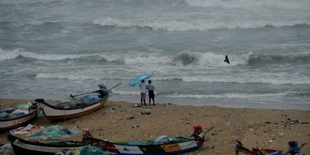 Residents walk near boats as waves break on the cost of the Bay of Bengal in