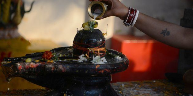 File photo of Indian Hindu devotees offering prayers to a Shiva Lingam, a stone sculpture representing...