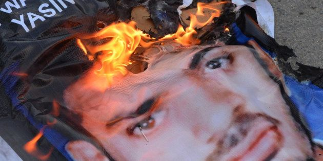 A poster of Yasin Bhatkal, an alleged founder of the Indian Mujahideen, burns after being set on fire...