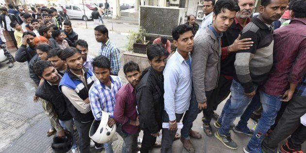 People stand in a queue outside banks to deposit and exchange old denomination Indian rupee 500 and 1000...