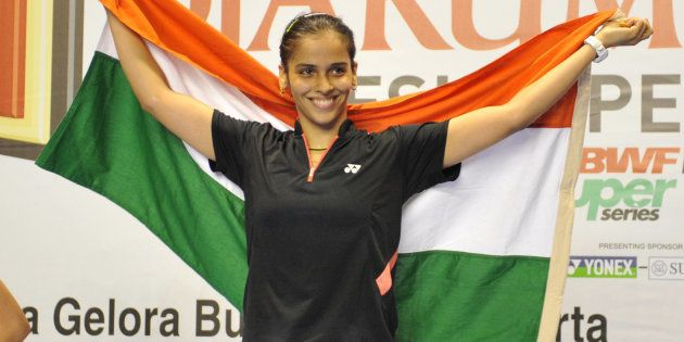 File photo - India's Saina Nehwal waves the Indian flag during the women's singles final medal ceremony...