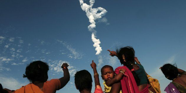 Indian bystanders look on as Space Research Organisation's (ISRO) satellite INSAT-3DR, on board the Geosynchronous...
