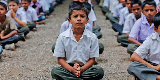 Students pray during a morning assembly at a school in the Ralegan Siddhi village, located in the Ahmednagar...
