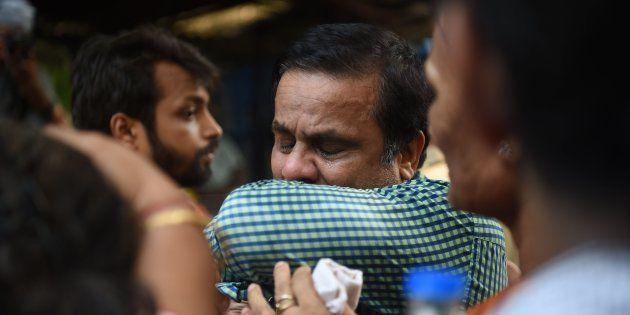 An Indian relative of a victim of a stampede on a railway bridge reacts outside a mortuary where bodies...