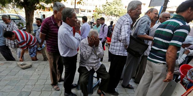 A man sits in a queue to deposit or exchange his old high denomination banknotes outside a bank in Ahmedabad,...